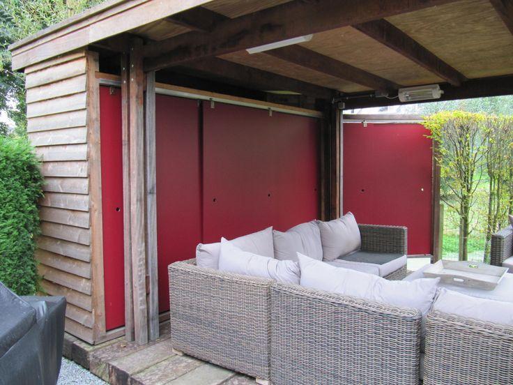 Een modern, strak afdak. Achter de rode schuifdeuren is bergruimte.