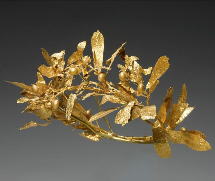 Greek gold olive wreath, 4th century B.C. Composed of two olive tree branches bound together at the back with spiral-twisted wire, with lateral shoots of centrally-ribbed leaves and berries attached by long wire stems; the front leaves showing signs of fire damage. Width approx, 24 cm width. Private collection