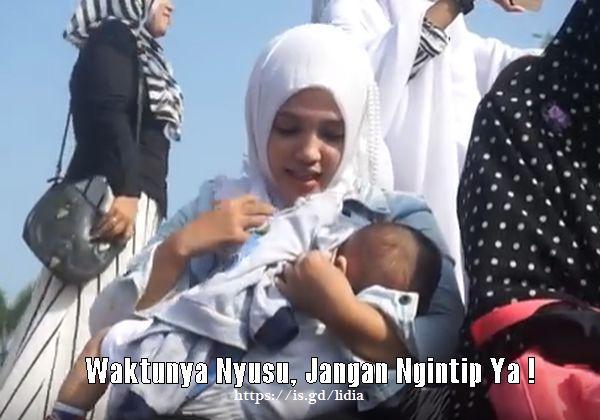 Photo ibu muda cantik berjilbab sedang menyusui anak