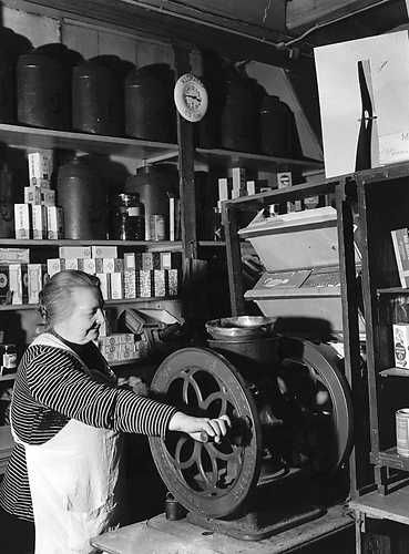 1951. Marie Keizer operating the coffee grinder in her grocery store, where everything is done manually. She does it for forty years this way and she feels automation is not necessary. Photo ANP Historisch Archief Community,  Amsterdam. #amsterdam #1951
