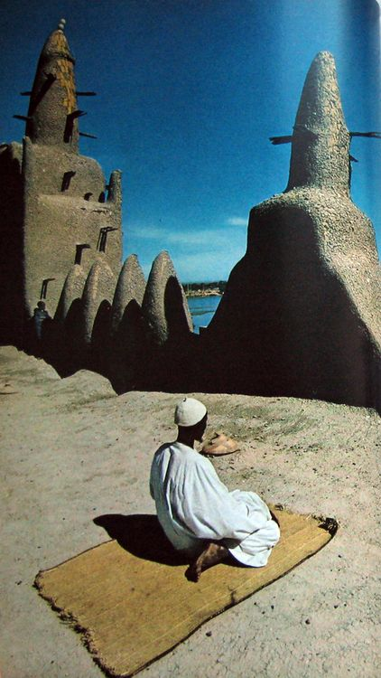 """""""Far from his spiritual home, an African Muslim faces Mecca during prayer in Mopti, Mali, a trade center on the southern rim of the Sahara. His rooftop outpost on the sunbaked mud mosque overlooks a branch of the Niger River.""""  Photograph from """"The Sword and the Sermon"""" by Thomas J. Abercrombie, published in the July 1972 issue of National Geographic."""