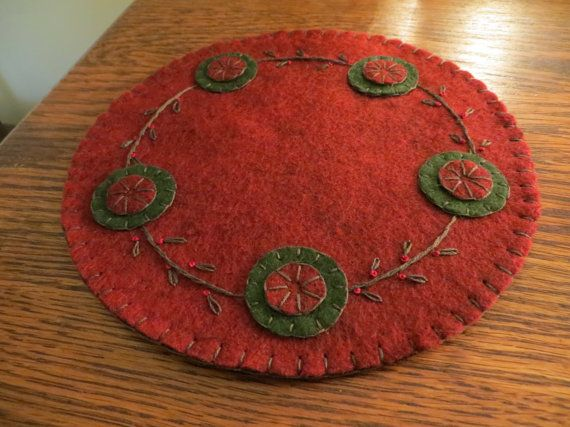 I made this penny rug with Christmas in mind-made from dark red and dark green felt and embroidered/appliqued with dark green floss-dark red floss for