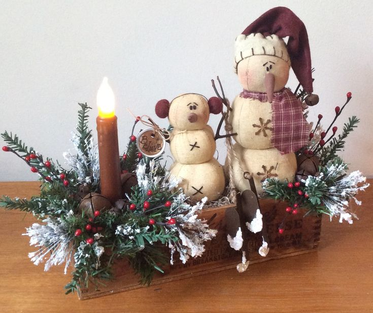This vintage cheese box is filled with two prim snowmen sitting on a bed of spanish moss and embellished with pine, frosted ming, laquered berries, pip berries, rusty jingle bells, frosted ice skates a grungy hang tag and a battery operated, wax coated flicker candle.