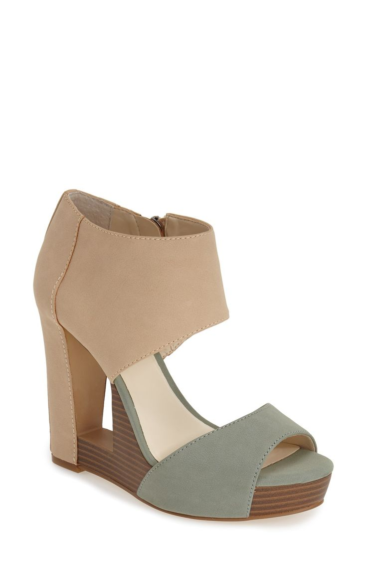 A dramatic cutout wedge adds architectural appeal to a two-tone sandal with an ultra-modern aesthetic.