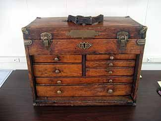 Antique oak machinist's tool box with hinged lift top.