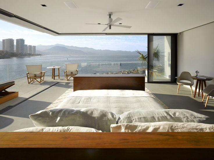 Une des chambres avec des énormes baies vitrées donnant sur un beau balcon et vue