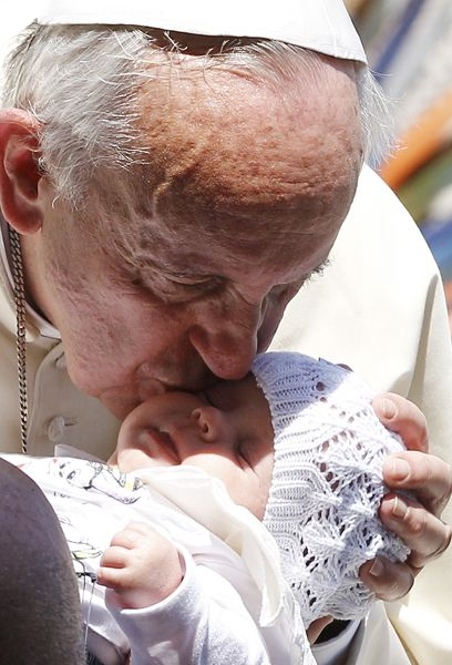 Pope Francis kisses a sleeping baby as he leaves his general audience in St. Peter's Square at the Vatican May 21.