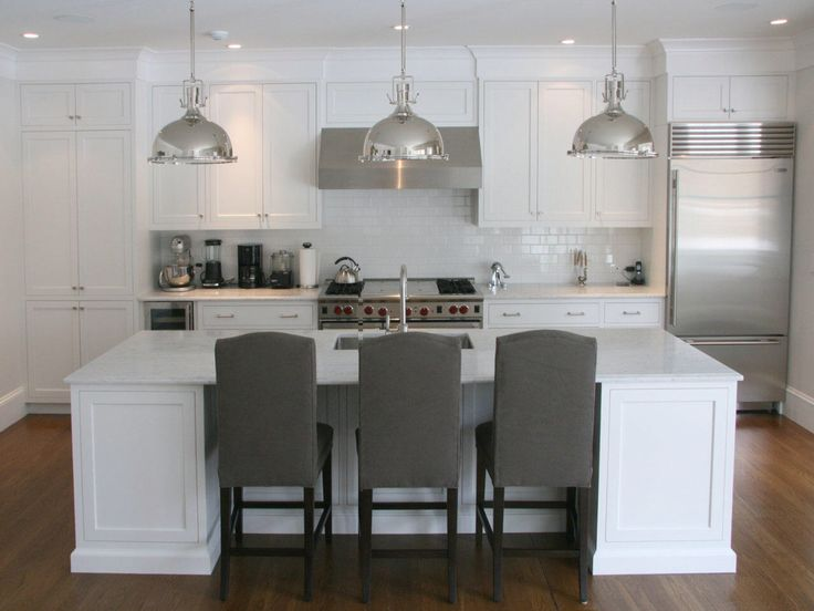 This Hamptons inspired kitchen features polished nautical pendants for island bench task light. The polished chrome tapware and accessories connect to create a theme whilst the stainless steel is consistently used for appliances. The marble top gives much needed pattern whilst connecting the white and grey tones. The stools add an element of drama through contrast. The floor adds warmth to the achromatic scheme.  Photo credit: amywerfel-interiors.com