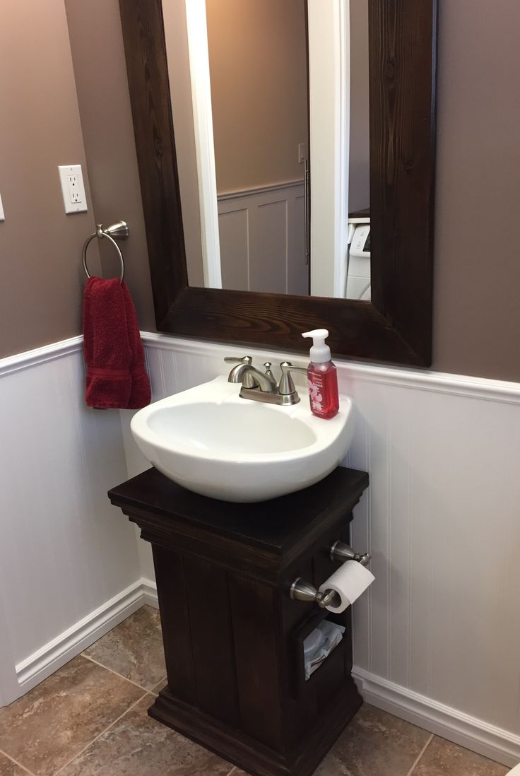 Removed the narrow ceramic pedestal from the half bath sink in favour of this walnut base. The recessed cubby for the wet wipes beneath the toilet paper is handy. Added a heavy wood frame to an old plain mirror to finish it off.