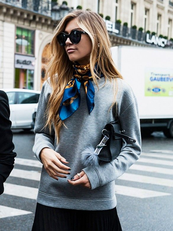 A gray sweatshirt is worn with a black skirt, silk scarf, black mini Hermes bag, and round sunglasses: