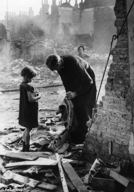 An East End parson with a child among the bombed ruins of London