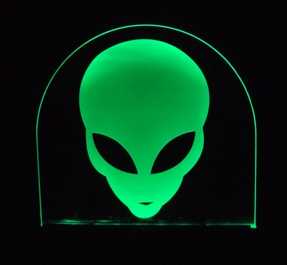 """$42 - Green Alien Edge Lit acrylic art: Space out on this unique etched Acrylic sign that features an enigmatic Alien, whose mysterious stare will add character to any space.    Frosted Acrylic has been laser frosted and lit from below with long lasting green LED lights.     This piece gives off enough light to add a celestial glow to your room.     Wooden base has UL listed, easy disconnect cord, for on/off functions. Dimensions are 6"""" wide by approx 8"""" tall."""