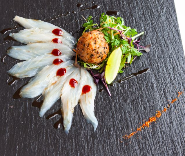 Seabass Sashimi Deluxe: Thinly- sliced Wild Seabass, Asian Style Crispy Rice Ball, Tangy Plum Rum Sauce & Ponzu Caramel served with a Micro Sprout Salad