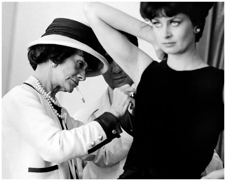 Fashion designer Coco Chanel adjusts the armhole of a model's dress with an assistant - Photo Douglas Kirkland