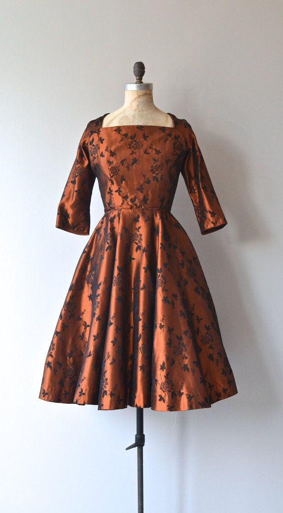 Vintage 1950s metallic copper satin dress with black floral embroidery, squared neckline, 3/4 sleeves, fitted waist, full skirt and metal back zipper.