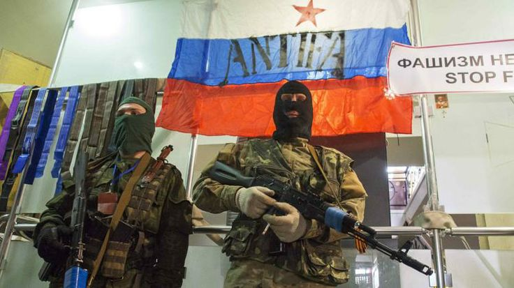 Pro-Russian armed men stand guard seized office of SBU state security service in Luhansk