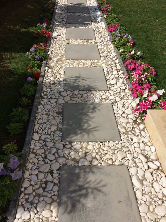 Cement block tiles bordered by white pebbles for a simple pathway: