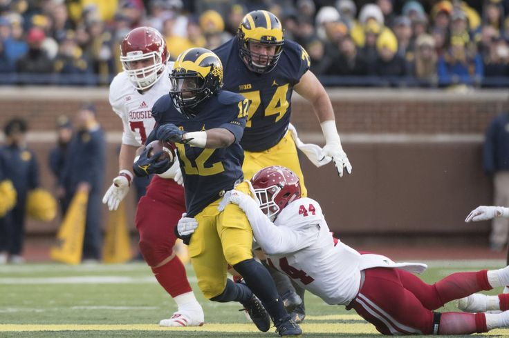 Michigan running back Chris Evans is tackled by Indiana's Marcus Oliver in the first quarter.
