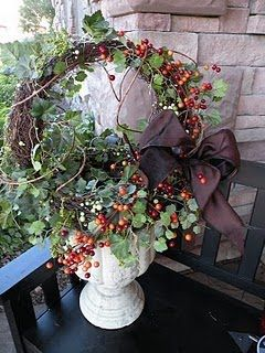 circular topiary in front porch pots decorated in the fall colors for this year...maybe...C.