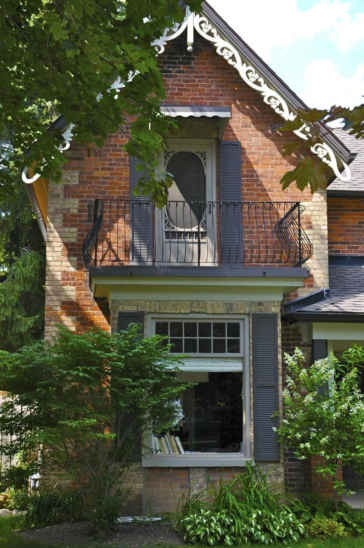 Zina St. Century home with iron railing balcony, white gingerbread cornice, brick quoining, and large front window with dark shutters.