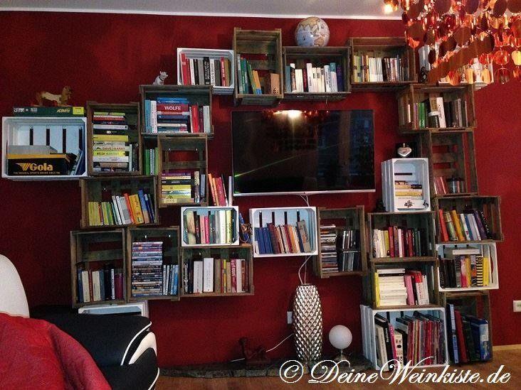 Hängende Weinkisten (mit Anti-Holzwurm-Wärmebehandlung) an roter Wand um TV herum