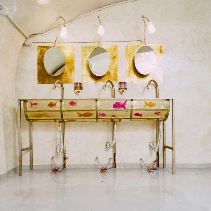 parete malta calce spessa lucida pavimento in resina lavandino pezzo unico in acciaio e resina con inserti