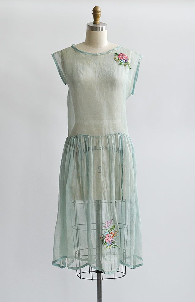 1920s flapper dress in soft mint green cotton organdy. This vintage 20s dress features drop waist, extended short sleeves, and wider round neckline. The sweetest embroidery adorns one side of the bodice and on the center front hem of the dress. Trailing silk ribbon and bow accents the back. Slip will be required.