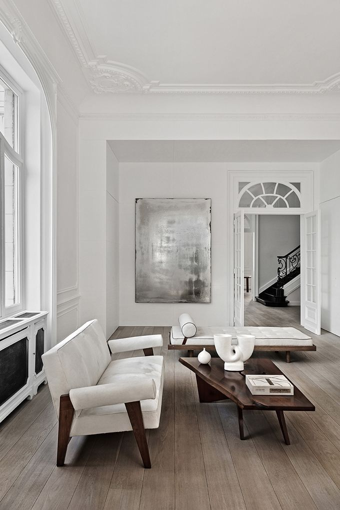 Stunning all white living room with wood details and beautiful wood moldings and trim.
