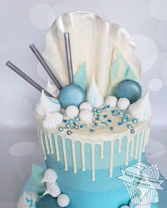 Blue ombré drip cake with lustered macaroons, meringue kisses and a chocolate sail