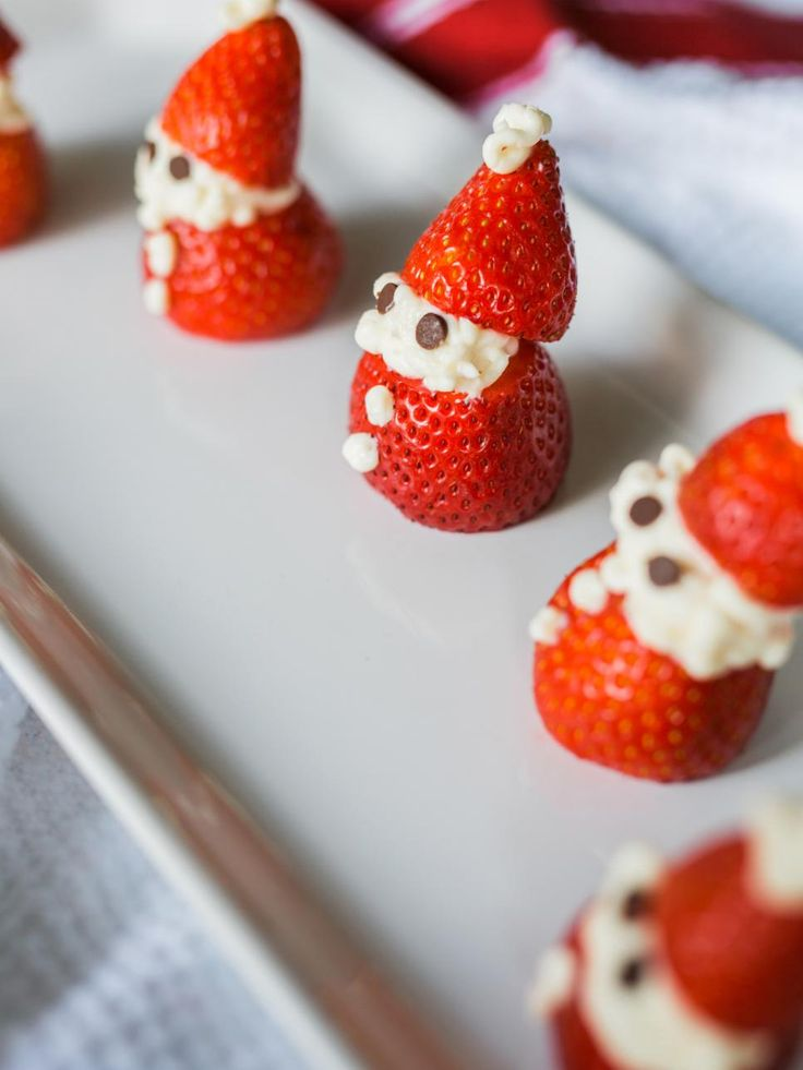 Create a flat surface on both ends of an upturned strawberry and use piped white icing to create these adorable snowmen Santas.