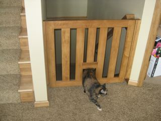 """Gatekeeper"" pet safety gate with cat door from a builder in Milwaukee WI.-ship nationwide self-installation kits High quality hardware, easy-to-use hidden mechanism, sliding hinge-easy to remove, only swing outward away from the stairway. Available in varied wood types including Oak, Maple, and Cherry or custom stained; special polyurethane for pet gets, custom designed- measured to fit to your home's specifications."
