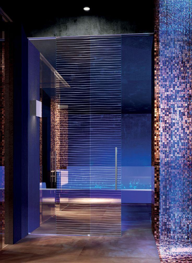 Porte scorrevoli esterno muro Inside, vetro stratificato trasparente extralight, decoro sabbiato bianco Dune, doppio maniglione tondo da 600 millimetri in acciaio, scorrimento incassato nel cartongesso.