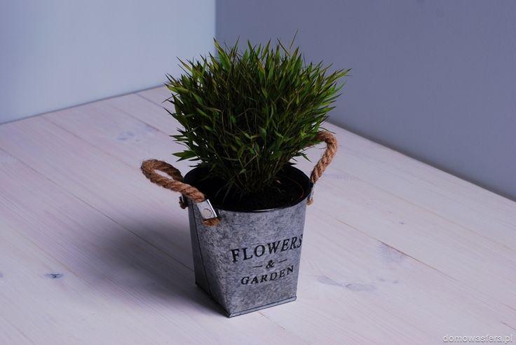 """Metalowa doniczka, która jest ocynkowana. Zdobi ją czarny napis """"flowers garden"""" oraz linka jutowa po bokach. Idealna pod uprawę pachnących ziół... i nie tylko. Sprawdzi się w domu, na tarasie lub ogrodzie."""
