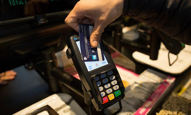 The rise of the cashless city: A customer uses a credit card to make a contactless payment.