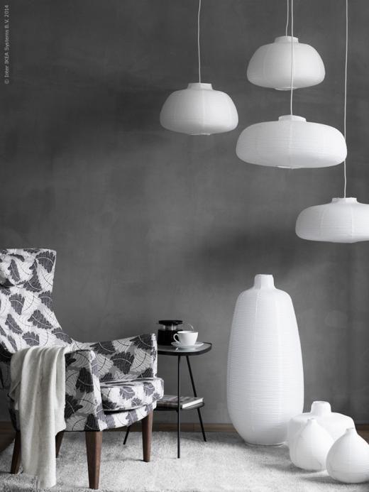 Grupper av lampor är både vackert, stämningsfullt och ljusstarkt. STOCKHOLM fåtölj med hög rygg, Mosta grå, VÄTE taklampskärmar och VÄTE golvlampor.