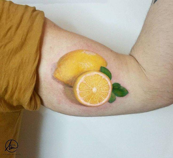 Tatuaje realista de un limón y medio en el interior del brazo izquierdo.