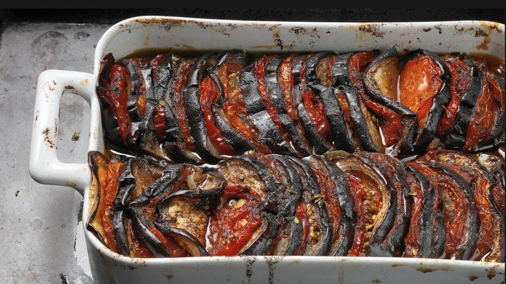 Visuals count, especially when appetites wilted by summer heat need a pick-me-up. The look of this eggplant and tomato casserole is just the thing, the glossy purple of the eggplant offset by the red stripes of the sliced tomatoes that have been wedged gently into the eggplant before baking.