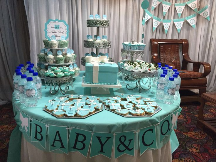 """Baby & Co"" themed baby shower table. Made Tiffany blue chocolate dipped strawberries, Tiffany blue macarons, onesies and bibs butter cookies, blue velvet cupcakes, Coutain candy mousse and even customized the bottle water"