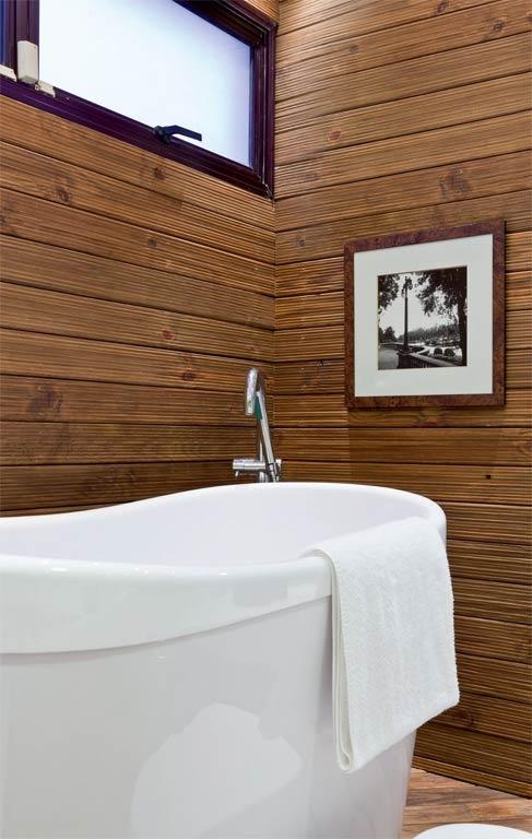 """Os antigos azulejos escuros começaram a incomodar os moradores, que também ansiavam por uma gostosa banheira de imersão. Foi preciso apenas colocar em cena a criatividade da arquiteta Melissa Dallegrave, que definiu uma área para a banheira usando deques de bambu (Natur Pisos) na parede. """"O acabamento com verniz marítimo garante a resistência da madeira, necessária a uma superfície constantemente molhada. Esse revestimento também trouxe conforto térmico para o canto"""", diz Melissa."""