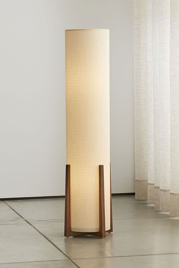 A Tall Cylinder Shade Of Natural Rattan Fabric Has A Tweed Effect