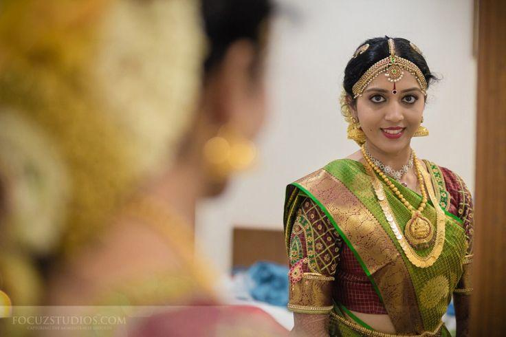 South Indian bride. Gold Indian bridal jewelry.Temple jewelry. Jhumkis.Green and maroon red silk kanchipuram sari.Side braid with fresh jasmine flowers. Tamil bride. Telugu bride. Kannada bride. Hindu bride. Malayalee bride.Kerala bride.South Indian wedding.