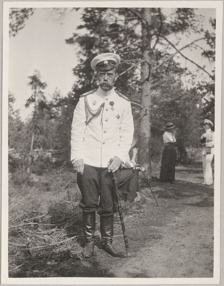 Czar Nicolau II, em 1914. Ao fundo da imagem pode-se vê duas de suas filhas as Grand Duchesses a coversar com um oficial.