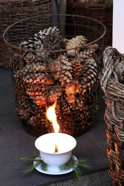 An old wire basket, pinecones and a cup and saucer with a lit candle. Simple and so charming