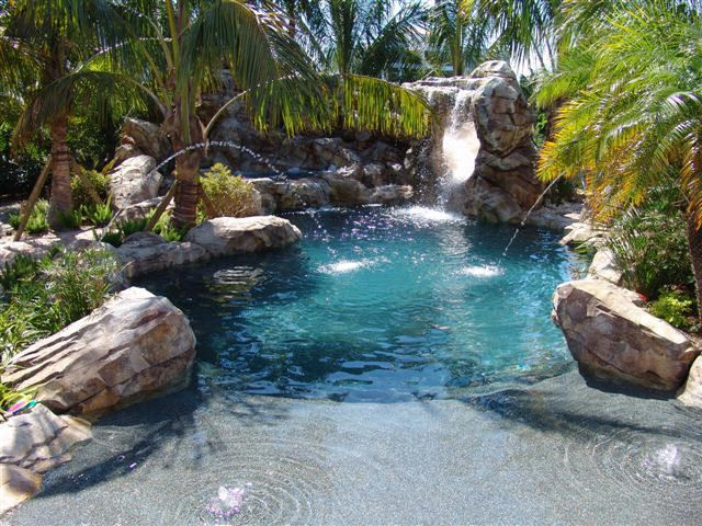 Custom Lagoon Swimming Pool Designed and Built by U.S. Pool, with beach entry, extra large spa, and a 20' slide wrapping around a 12' high waterfall.