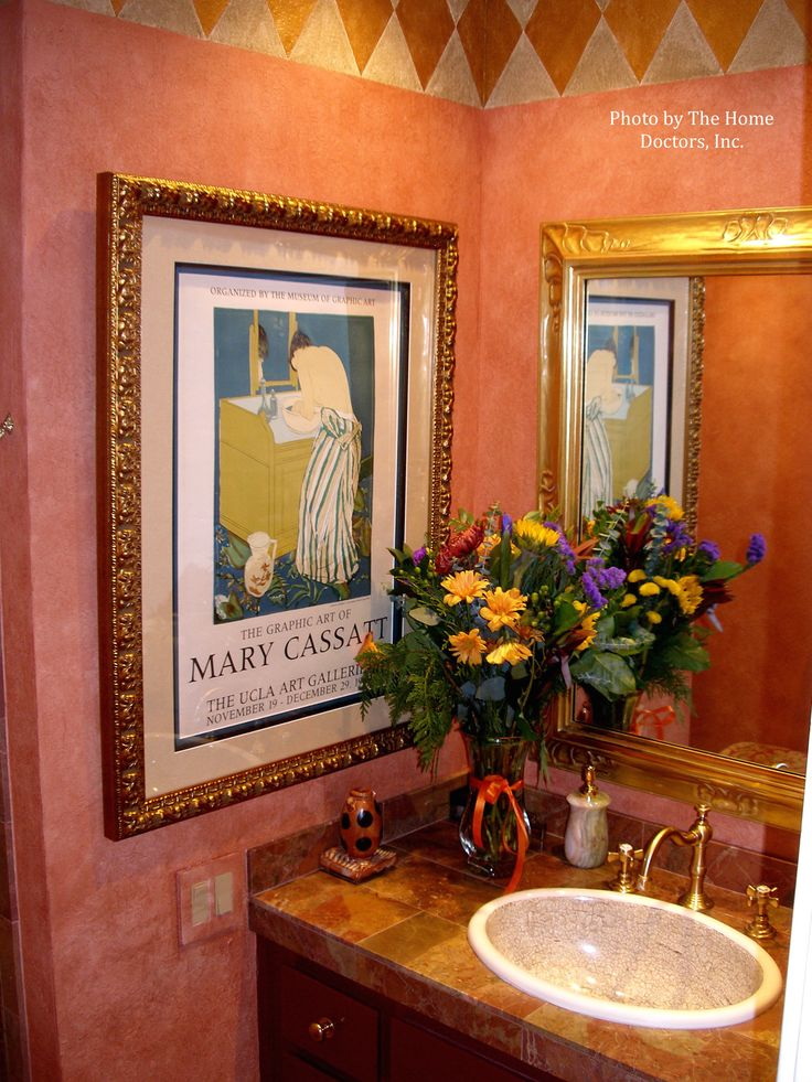 Bring life to your small bathroom with pink painted walls, and gold painted wall accents to match your gold cabinet hardware. Spruce up this vintage look with a bright floral arrangement. #mixandmatch #bathroomdecor