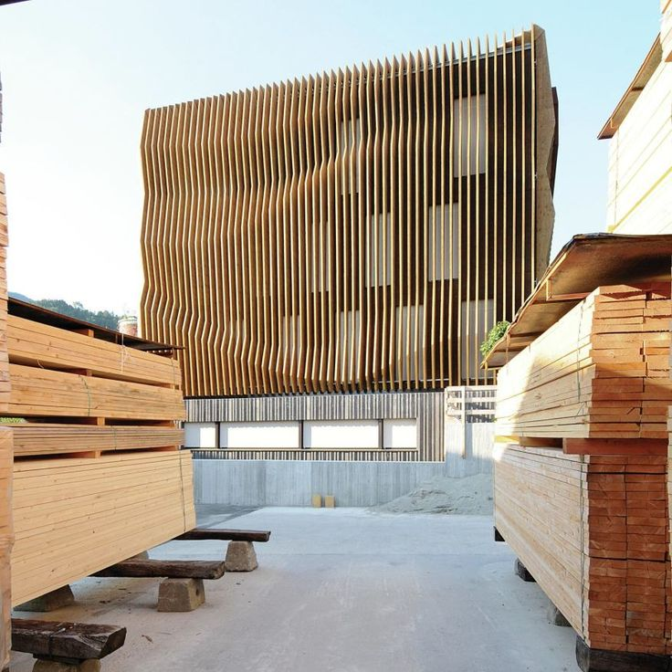 The plywood fins that wrap Damiani-Holz & Ko'sheadquarters mimic the pallets of boards and planks in its lumberyard.