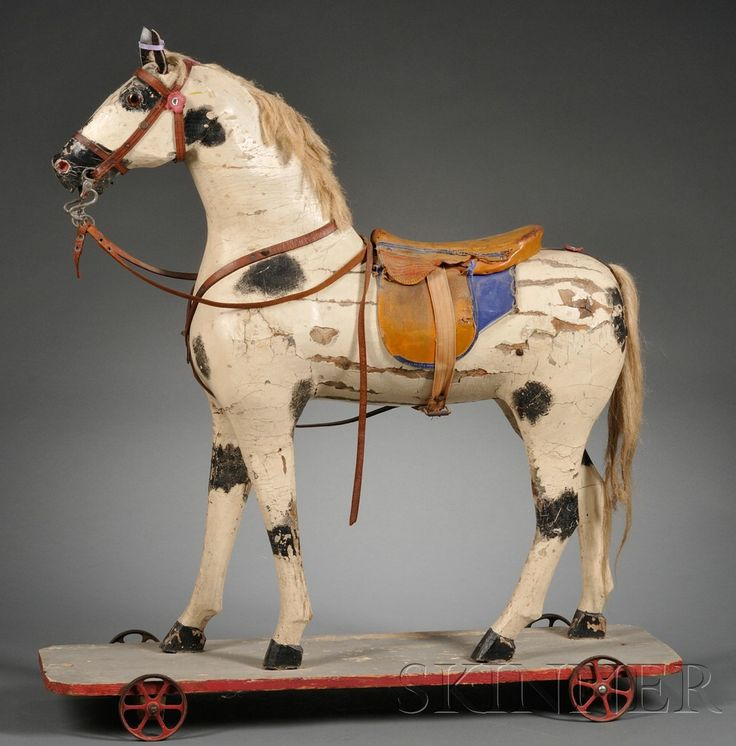 Painted Wooden Horse Pull-toy, late 19th century, with glass eyes, leather ears, harness, and saddle, horsehair tail, mounted on a wooden platform with cast iron wheels, old repaint, (paint losses, replaced ears, leather losses), ht. 33, lg. 32 in