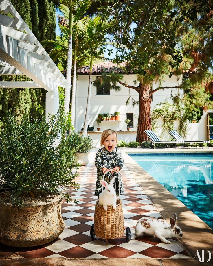Nate Berkus ad Brent's Gorgeous LA Home | Poppy in aBonpointdress, pushes a wheeled basket byFire and Creme Kidswith Harvey (in basket) and Swiggen, two Rex Cross rabbits. Pool deck clad inGranadatile.
