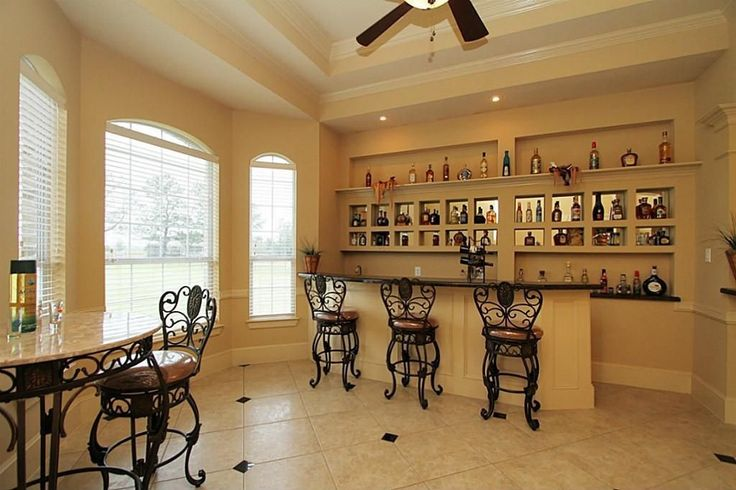 Eclectic Bar with Arched window, Built-in bookshelf, Ceiling fan, Concrete tile