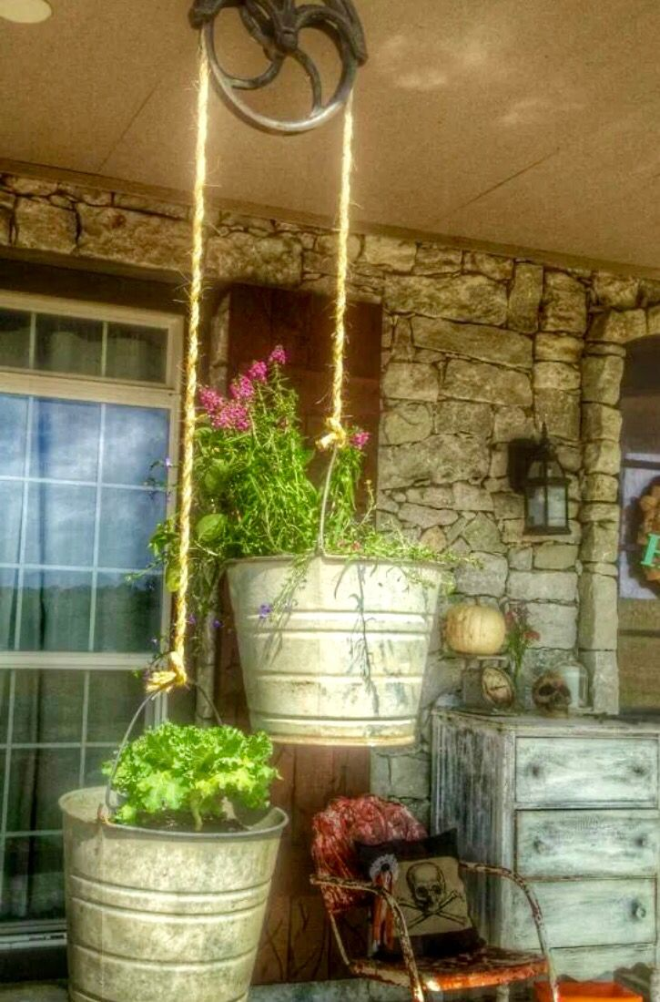 Love this idea of an old pully and buckets for planters! Hang from arbor with buckets